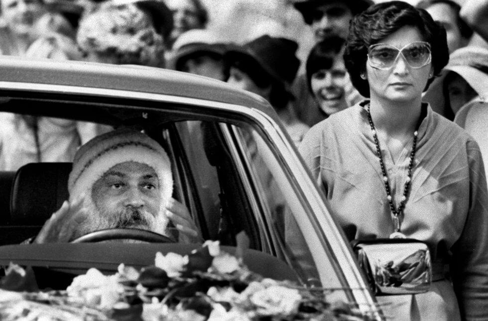 Baghwan em um dos seus 90 carros e Sheela ao seu lado